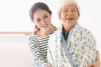 caregiver helping senior woman to wear a robe
