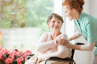 Young caregiver helping an senior woman in a wheelchair