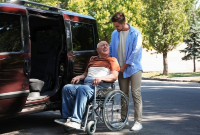 Young caregiver helping senior man in wheelchair to get in to van
