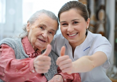 senior woman and caregiver are showing thumbs up