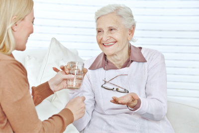 caregiver giving a medicine and glass of water to the senior woman