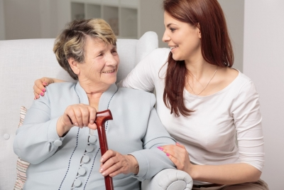 caregiver and senior woman are smiling while having a conversation