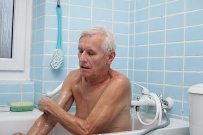 senior man washing his body with soap sponge in bath