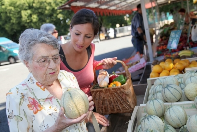 Young caregiver helping senior woman with grocery shopping